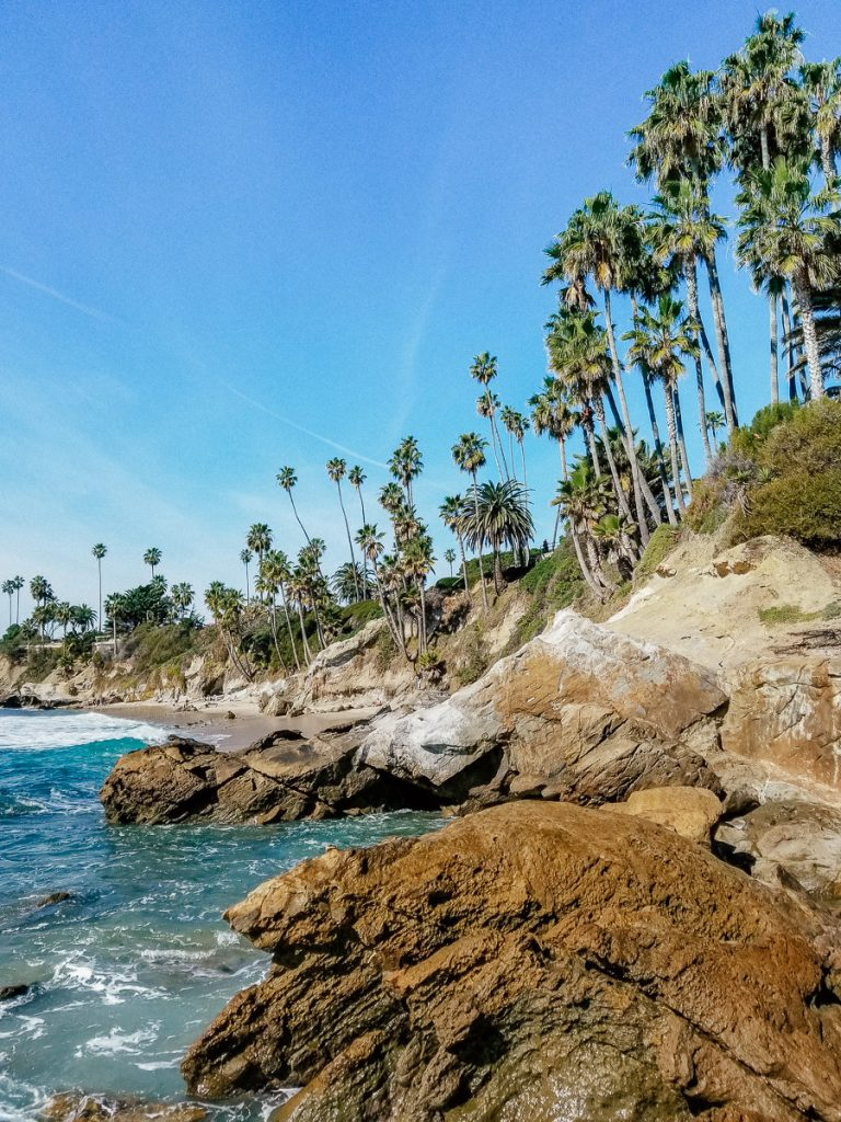 The rocky coastline at Rockpile Beach is lined with palm trees.